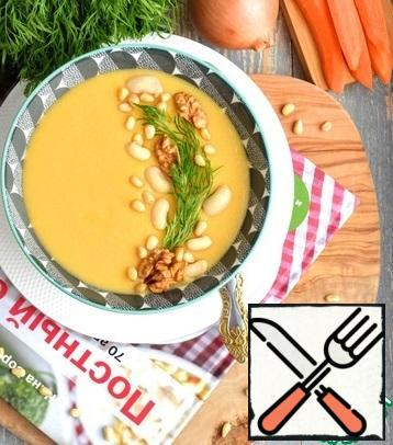 Ready-made soup-puree pour on plates, decorate with sprigs of dill and nuts, about 15 gram per serving