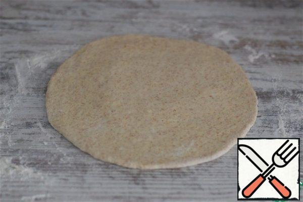 Place the dough on a work surface lightly dusted with flour, knead, and divide into four equal parts. You can make one large pie, two medium-sized pies, or several small ones. Molding - at your request! I cook 4 round pies like Ossetian ones. Roll out each part of the dough into a circle 3-4 mm thick.