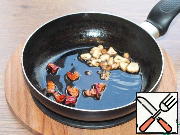 In the heated vegetable oil (3 tbsp. l.), fry the hot pepper and garlic cut into slices. Then we remove the vegetables, leave the oil.