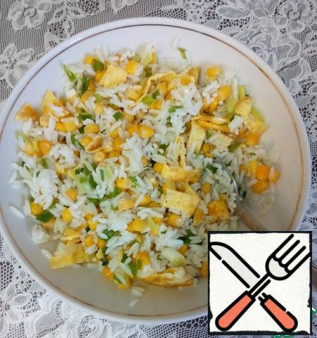 Shake the chicken egg with a pinch of salt using a whisk, pour into a non-stick frying pan, brown on both sides, transfer to a wooden board, roll and cut into strips, add to the rice and corn, mix.