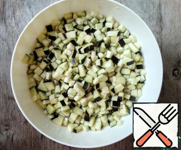 Then wash the eggplant, cut into cubes, add salt (0.5 tsp), mix, pour cold water, leave for 20 minutes to remove the excess bitterness. At the end of the time, drain the water.