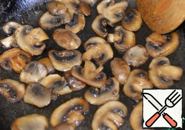 In a hot deep frying pan, pour half the amount of vegetable oil and fry the mushrooms over high heat until browned. Remove the mushrooms from the pan.