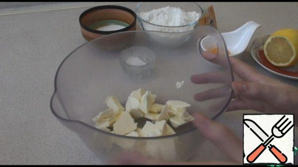 Butter from the refrigerator cut into pieces, add sugar, vanilla sugar, egg yolk, lemon juice, most of the flour, baking powder and knead the dough.