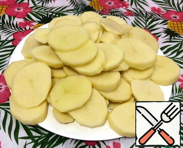 We crumble the potatoes in slices (not very thinly). It is better to do this manually (without using a food processor or grater). Too thick pieces are also not worth doing, as it does not boil much in tomato sour broth.