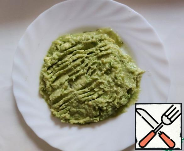 Cut the avocado in half, remove the bone. On a plate, mash the avocado with a fork and pour over the lemon juice. I needed 2 tablespoons.