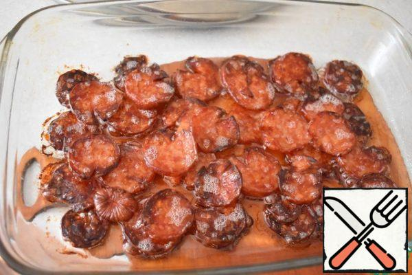 Preheat the oven to 150 g. Remove the skin from the sausage, cut it into thin rings and put it in a form greased with vegetable oil in 2 layers. Place in the oven and dry for 35-40 minutes.