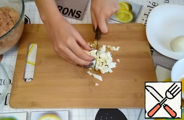 Prepare the filling for the minced chicken. You need to finely chop 2 boiled eggs.