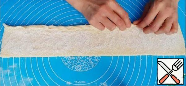The dough is divided into 2 parts and formed from each form a roller, roll out to a thickness of 2-3 mm and cut off the uneven edges. Then sprinkle the dough with sugar, coconut chips and distribute evenly over the entire surface. The dough is twisted into a tube, as tightly as possible and cut into identical pieces about the size of 5 cm