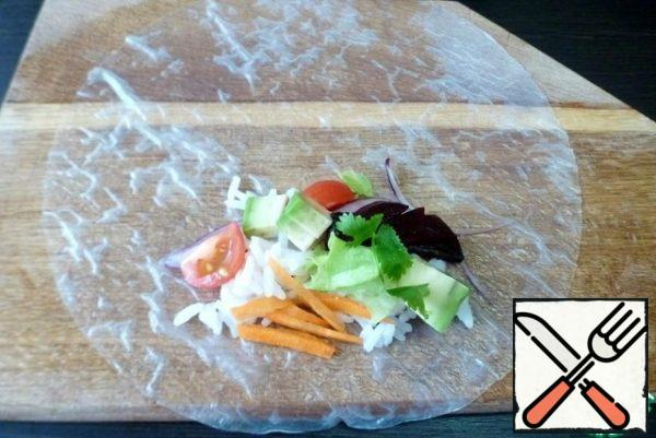 Put the rice paper on a wooden board. On one edge, put a little of all the vegetables and a spoonful of rice.