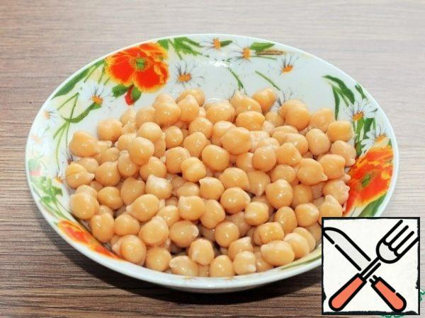 Pre-prepared chickpeas are boiled according to the instructions. The broth from the cooked chickpeas is drained into a bowl and removed to the side.