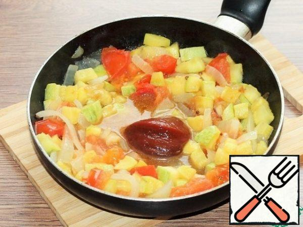 We push the vegetables to the edge of the pan, and put the tomato paste in the middle, fry it in vegetable oil for 1-2 minutes. Then mix the pasta with the vegetables.