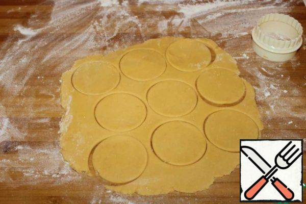 Divide the dough into two parts for convenience. Knead a little and roll out each piece into a layer 5 mm thick. Cut out circles with a diameter of 6 cm