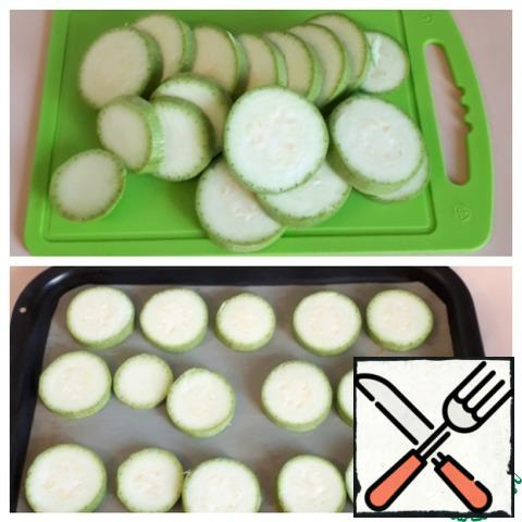Zucchini cut into 0.5 cm thick, spread on a baking sheet and bake in the oven.