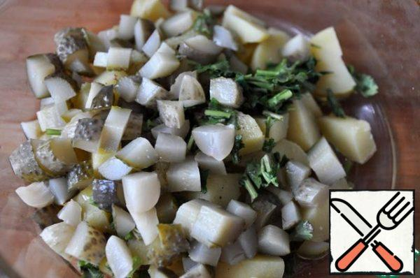 Add diced pickled gherkins and finely chopped coriander greens to the potatoes.