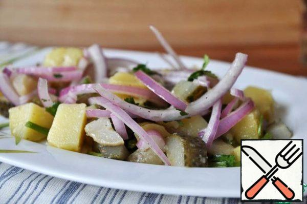 On a serving plate, spread the potatoes with gherkins and onions.