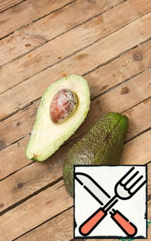 Ripe avocado leaves a trace on the skin when pressed with your finger, it is not hard to the touch, but rather soft.Cut the avocado in half in a circle, turn it and divide it into two halves, remove the bone.