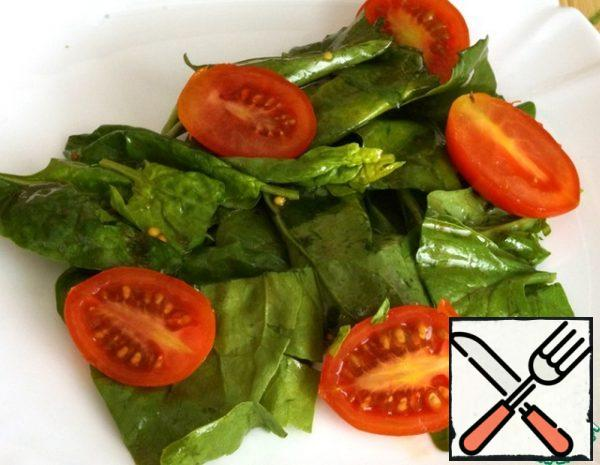 We begin to collect the salad. Put the seasoned spinach leaves on a plate, add the cherry tomatoes, cut in half.