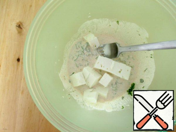 Add feta (100 g) to the dressing and mash it with a fork.