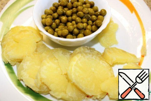Potatoes-slices, canned peas, throw in a colander, drain the liquid.