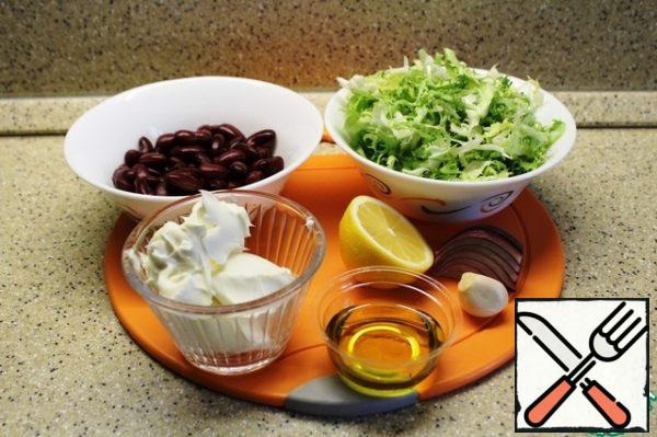 Products for making salad. Pre - drain the liquid from the beans and rinse with cold water.