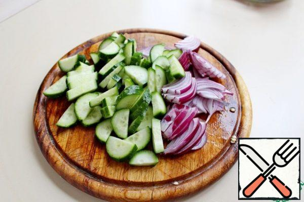 Cut the cucumber into small pieces. Salad red onion-feathers.