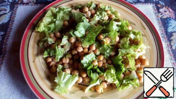 Now you can collect the salad. Place the coarsely chopped lettuce leaves on a serving plate, and place the chickpeas on top. Mix vegetable oil, mustard, vinegar, salt and pepper for dressing. Pour part of the dressing over the salad and chickpeas and mix everything slightly.