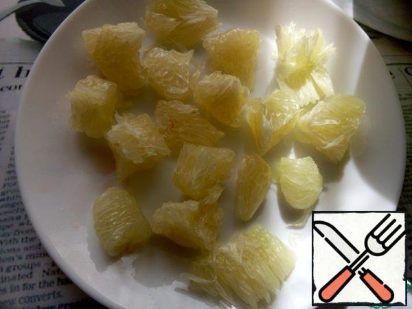 Clean the pomelo from the peel and films and disassemble it into small segments.