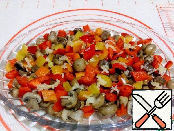 The first layer on the dish is laid with pickled mushrooms, diced Bulgarian pepper and crushed garlic.