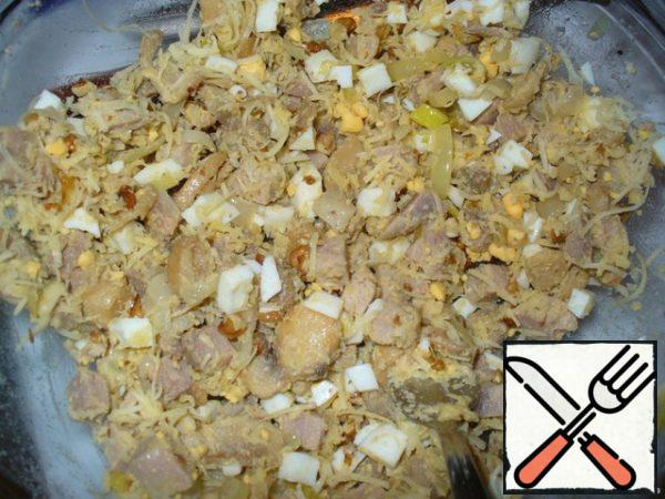 Boil the eggs hard-boiled. Cut them into cubes. In a salad bowl, mix the cubes of pork, fried mushrooms with onions, eggs, grated cheese and chopped walnuts.