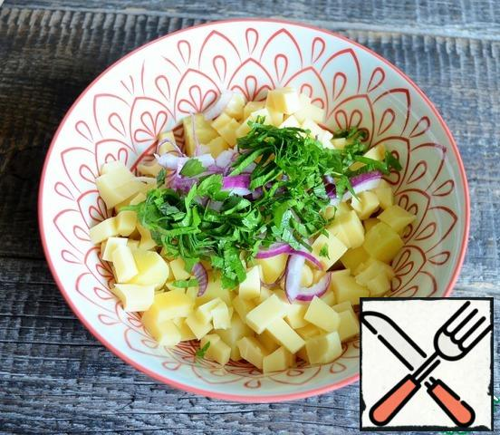 Wash the greens, dry them, chop them, and add them to a salad bowl. Also chop the red onion.