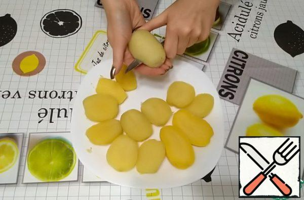 The cooled potatoes need to be peeled. Each potato is cut in half lengthwise.