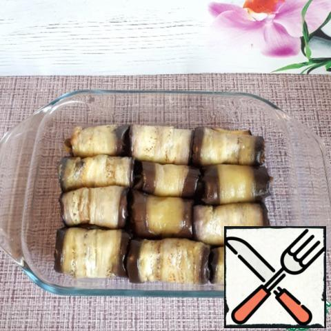All the other eggplants are also rolled into rolls with filling and put them in a deep container.