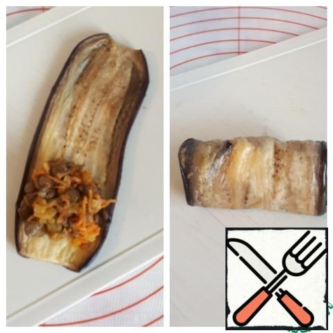 Now we take a plate of baked eggplant, put the lentil filling on the edge and roll it up.