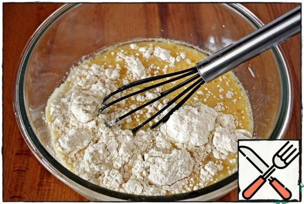 After that, add the milk, vegetable oil, and mix. Then pour out the flour, baking powder and mix well again.