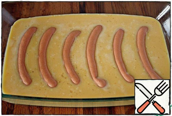 The baking dish is lightly greased with vegetable oil, pour the egg mixture into the mold, add the sausages and put in the oven, preheated to 180 degrees for about 25 minutes.