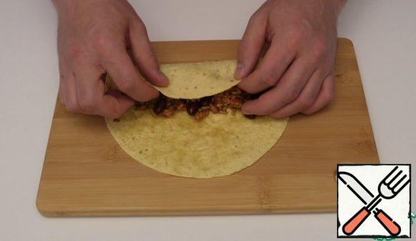 Next we put the tortilla spread our filling on it and twist it into a tube