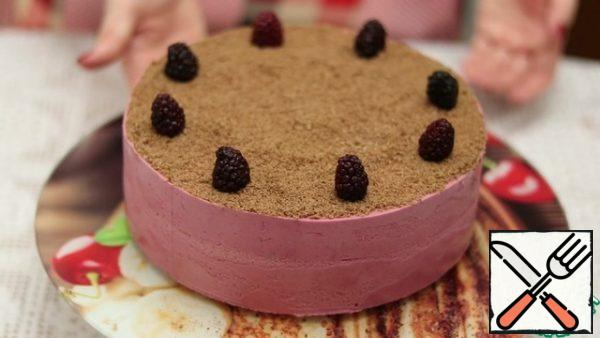 Decorate the cake with the ground remains of the cake and berries. Enjoy your meal.