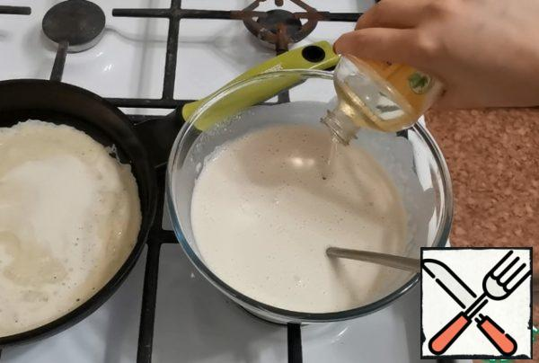 While the first pancake is being fried, add vegetable oil to the dough. Mix well. At the same time, the pan is no longer greased with oil.