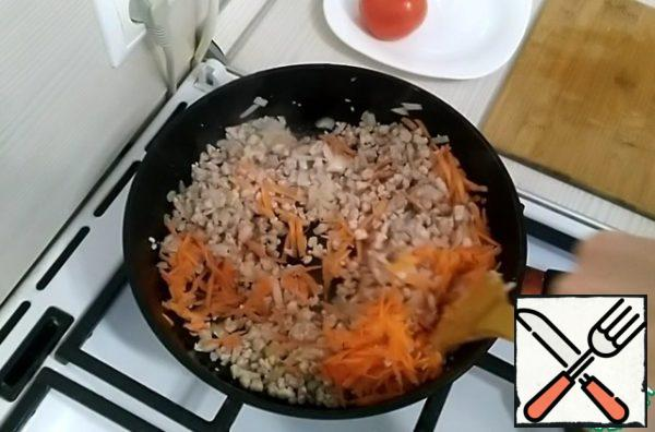 Meanwhile, grate the carrots on a coarse grater. Pour the carrots into the pan. Fry it.