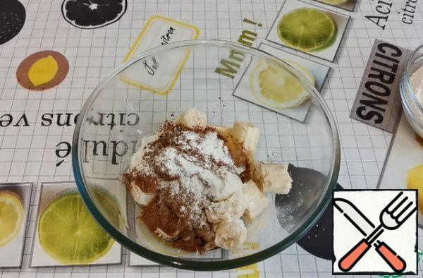 In bananas, we break the eggs. Add vegetable oil, cocoa powder, baking powder.