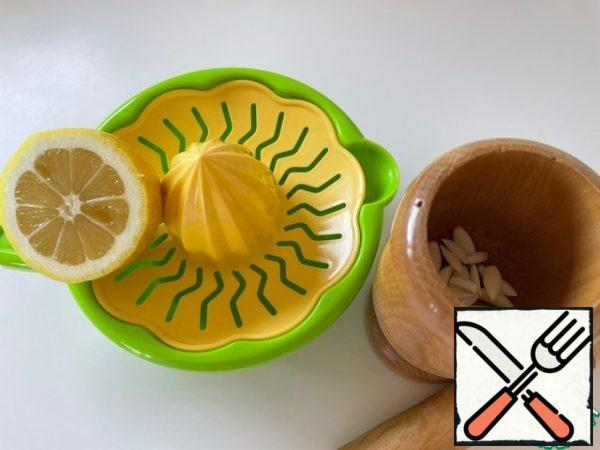 Squeeze out the juice from half a lemon. Chop the garlic with 1 tsp of salt.