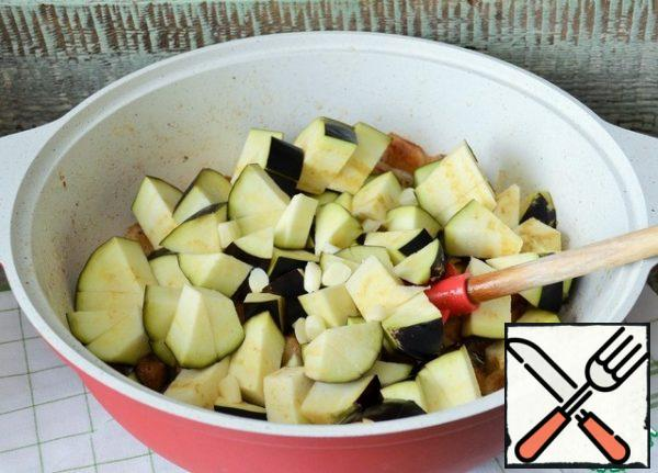 Add eggplant cubes and garlic slices. Fry for a couple of minutes over medium heat.
