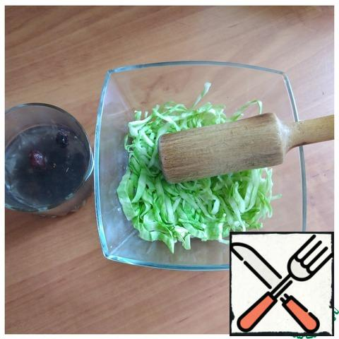 The raisins are steamed with boiling water for 5 minutes. The cabbage leaves are twisted into a roll and very thinly cut into long noodles. So in a salad, it will look more beautiful. Put the cabbage in a salad bowl and add a little salt. We beat the cabbage with a wooden mallet so that the cabbage gives juice. Young cabbage does not need to be beaten much, it is very juicy and crispy!