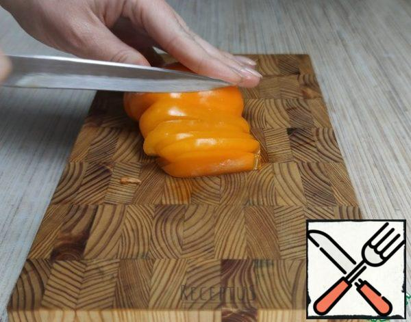 """While the chicken is in a bowl and marinated, I prepare a"""" pillow """" of bell pepper: I remove the core of the fruit, cut the pepper into thin long strips"""