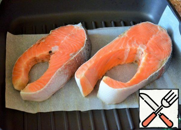Clean the fish, wash it, and dry it on a paper towel. Preheat the grill pan. Lay out the baking paper and put the steaks on it.