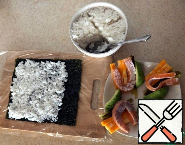 When the rice is cool, mix it with 3-4 tablespoons of cucumber brine. Mix well and divide into 4 parts. The rice should not be too dry or wet. Wash and peel the avocado. We also divide it into 4 parts, where each part is cut lengthwise into 2 pieces, so that it is enough for the entire length of the nori leaf. I recommend buying nori sheets with a stock, since dishonest manufacturers or sellers can cheat (in a branded sealed package, there may be 2 sheets less than the specified one; 8 instead of 10).