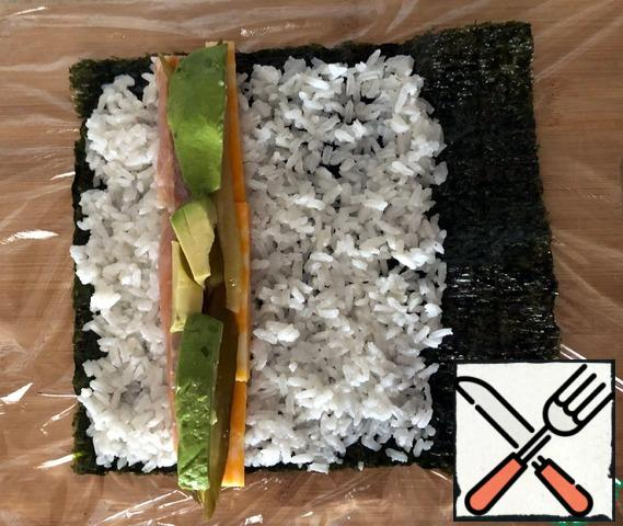 A large wooden board is lined with plastic wrap. If there is a special mat for making sushi, use it. We spread the sheet of nori with a smooth side to the film. A quarter of the rice is evenly distributed over 85% of the surface of the nori leaf, leaving a strip without rice somewhere from 3-4 cm. On the side covered with rice, step back 3-4 cm and lay a narrow strip of a quarter of the ingredients (salmon, cucumber, cheese, avocado)