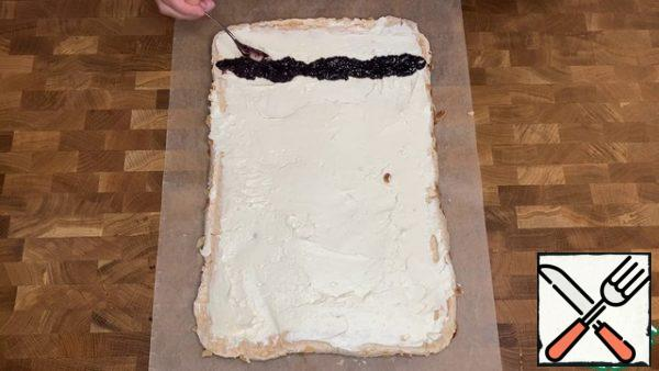 Turn the finished meringue over. Remove the parchment and allow to cool. Apply the cream to the cake. You can leave a little bit for decoration. Slightly retreating from the edge, make a strip of jam.