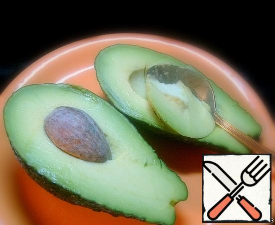 Cut the avocado lengthwise. With a spoon, we take out the pulp and cut it arbitrarily.