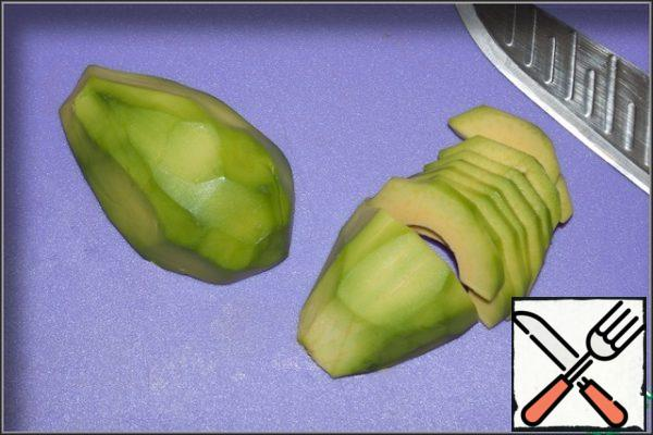 Peel the avocado, cut it in half, removing the stone, and cut it into slices.